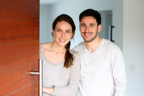 Happy couple opening new home entrance door